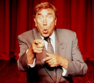 Comedian, Frankie Howerd, on stage.